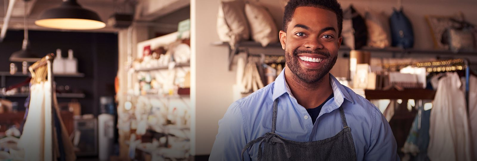 man in apron smiling in a store