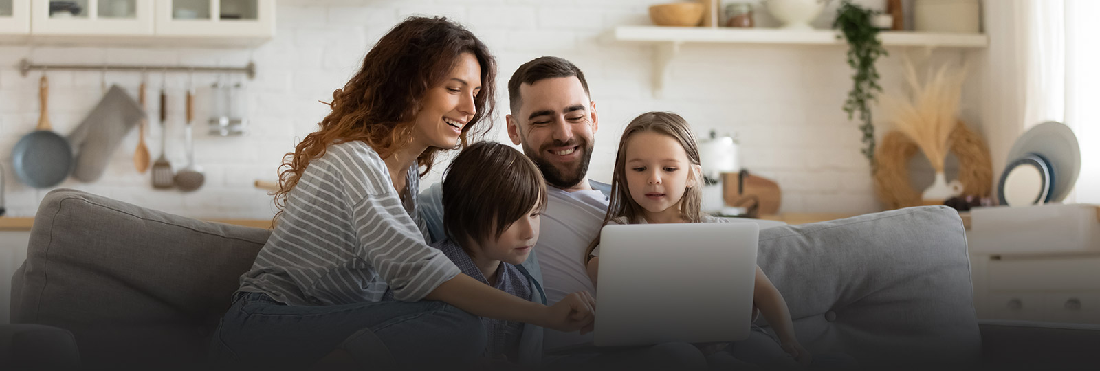family of four sitting on a couch looking at a laptop